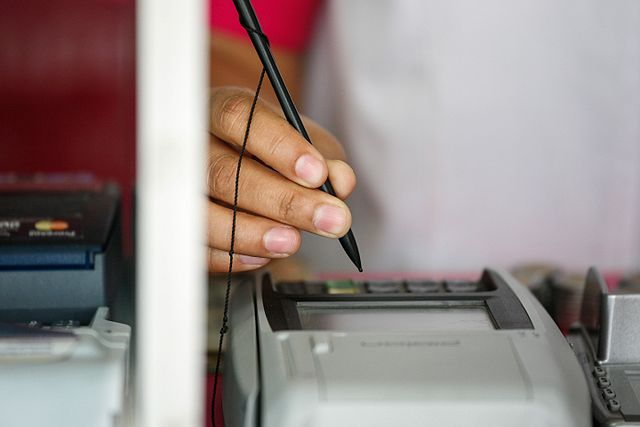 Finger with pen hovering over credit card machine